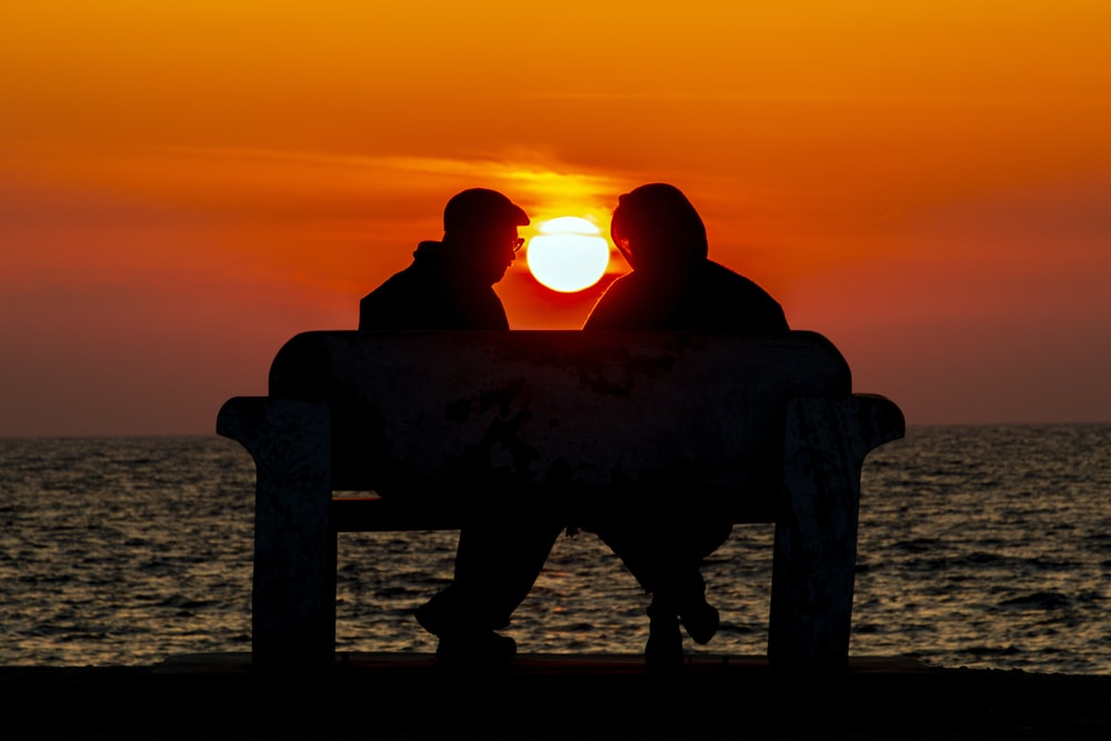 silhouette of man and woman sitting on bench while facing each other