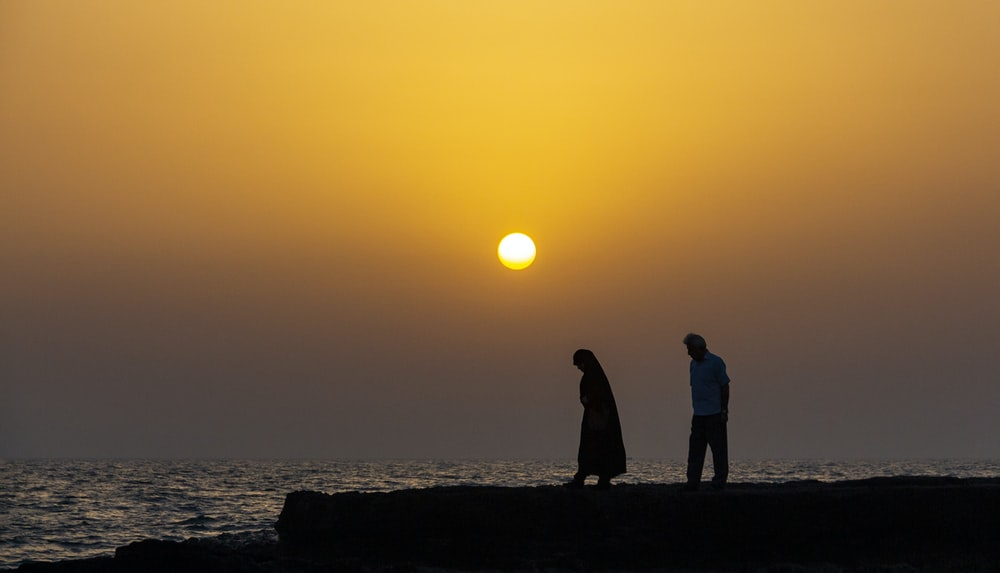 silhouette of man and woman by the body of water at sunset