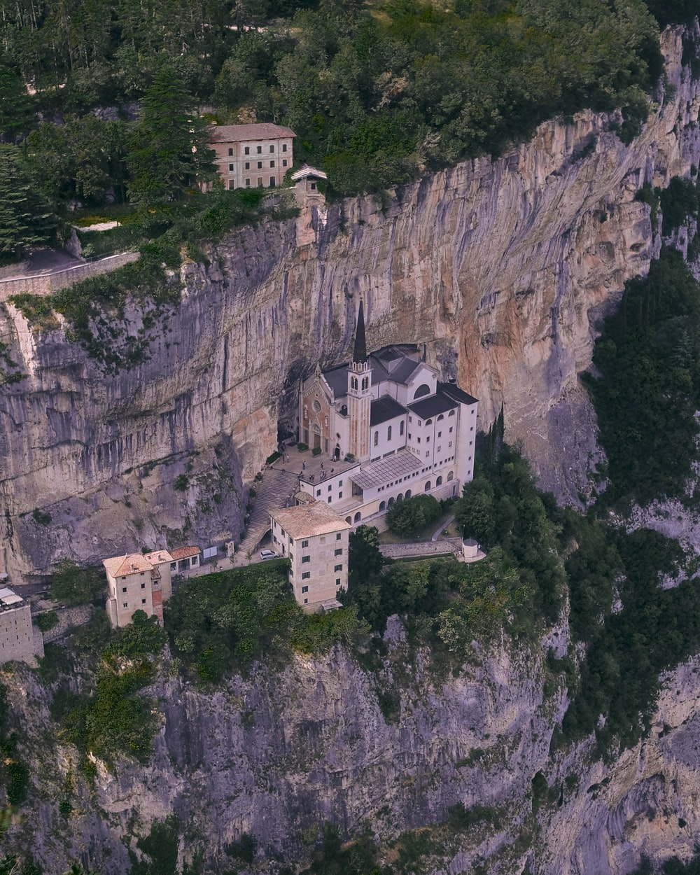 aerial photography of a cathedral on a mountain cliff