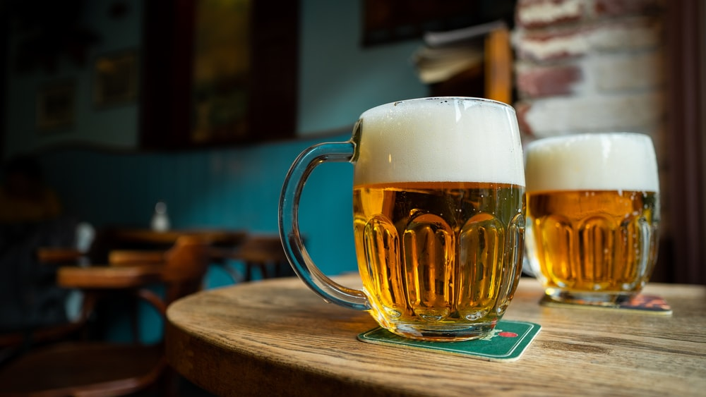 beer in clear glass mugs on round brown wooden table