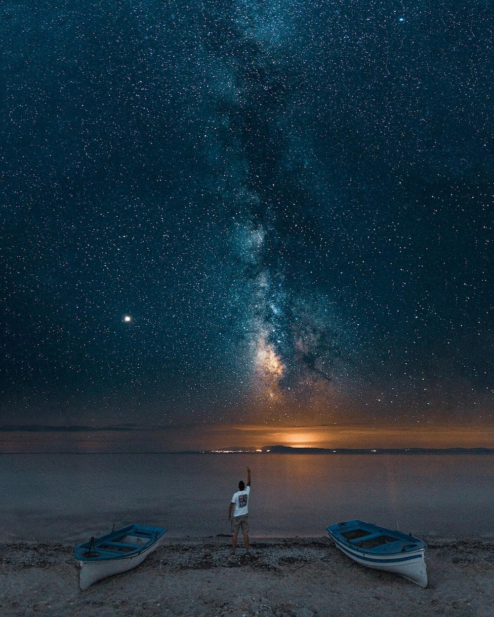 man standing between boats near sea