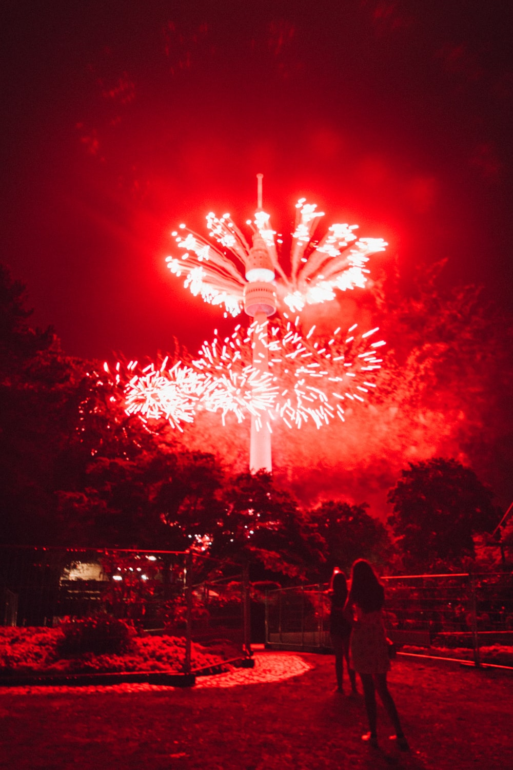 two person standing in front of red fireworks