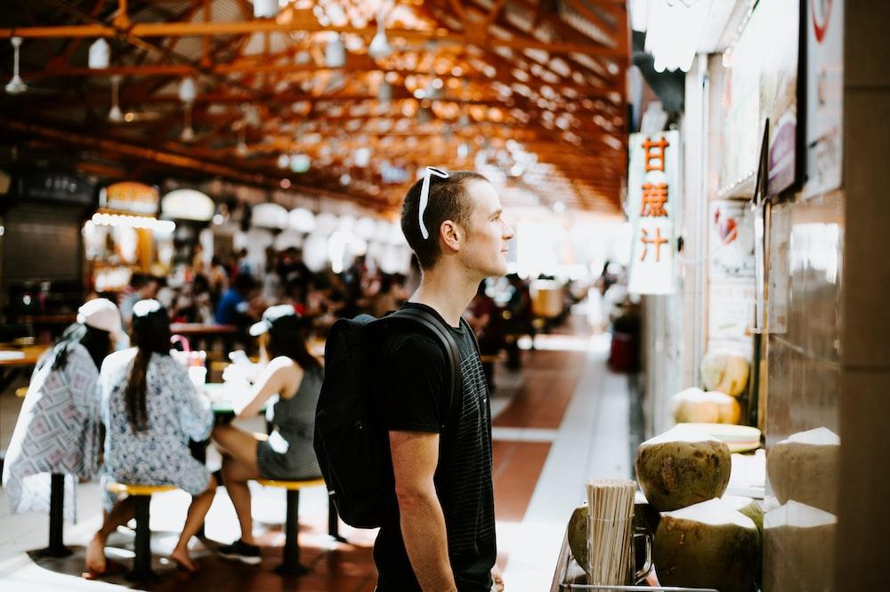 man wearing black shirt standing beside wall