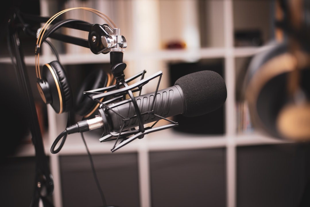 Side on a shot of a podcasting set-up with headphones and a professional microphone