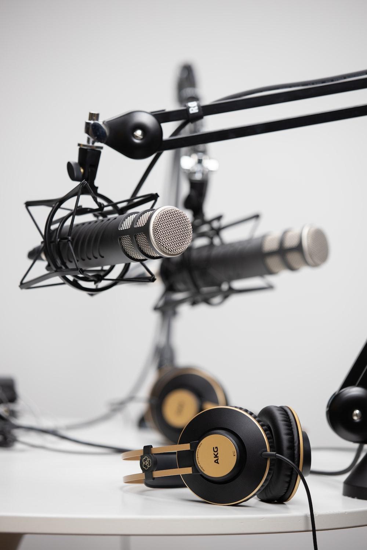 black and gold AKG corded headphones near black microphones