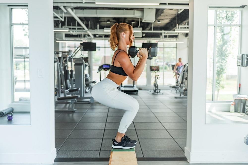 woman wearing black sports bra and white legging lifting dummbells
