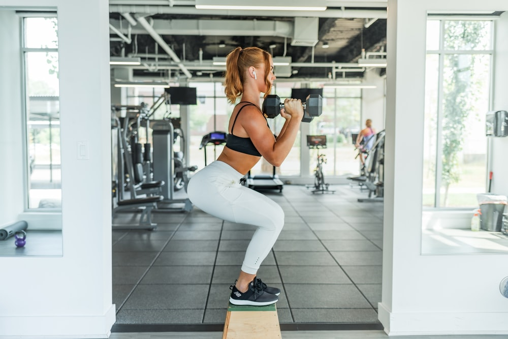 woman wearing black sports bra and white legging lifting dummbells