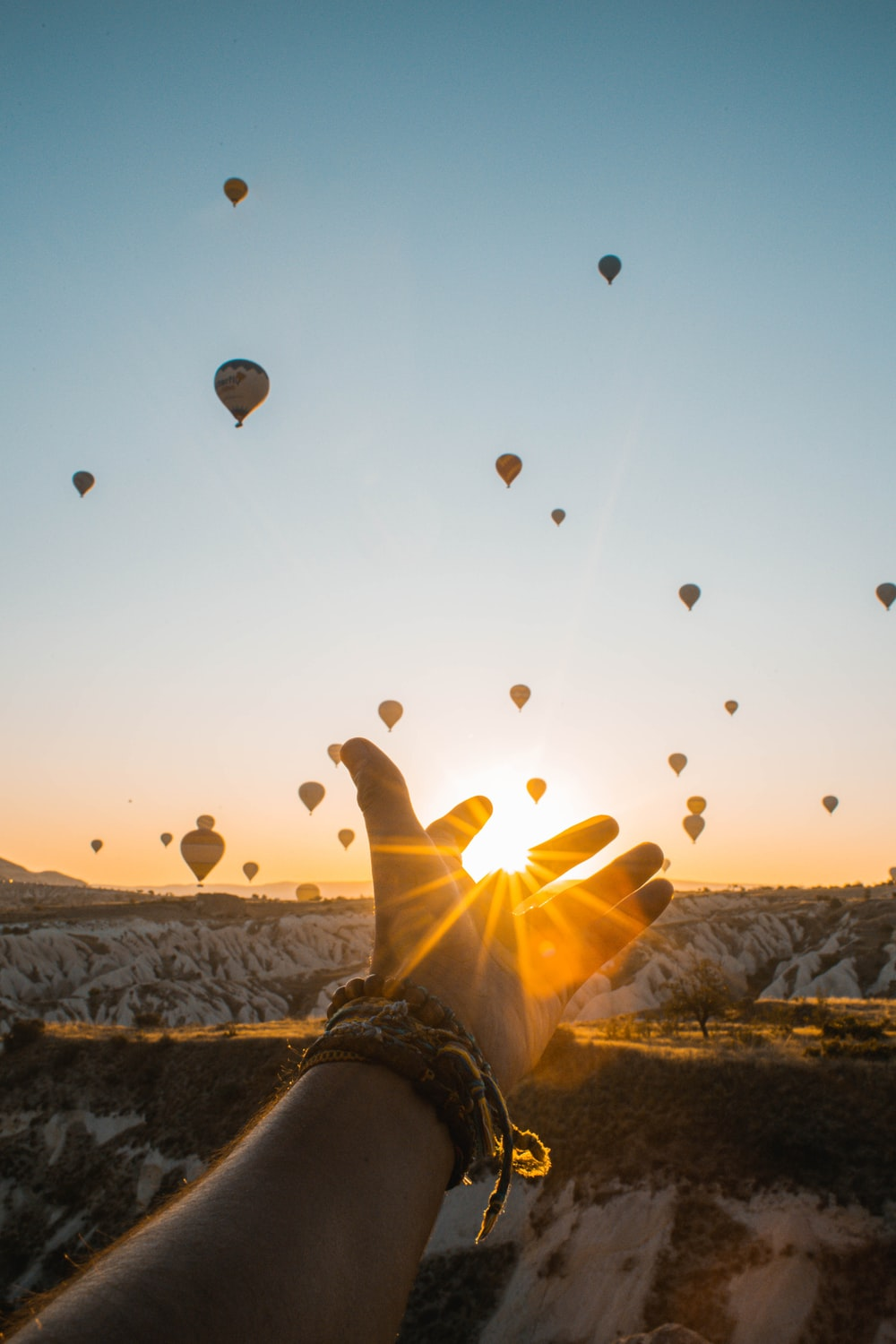 left human hand with air balloons background
