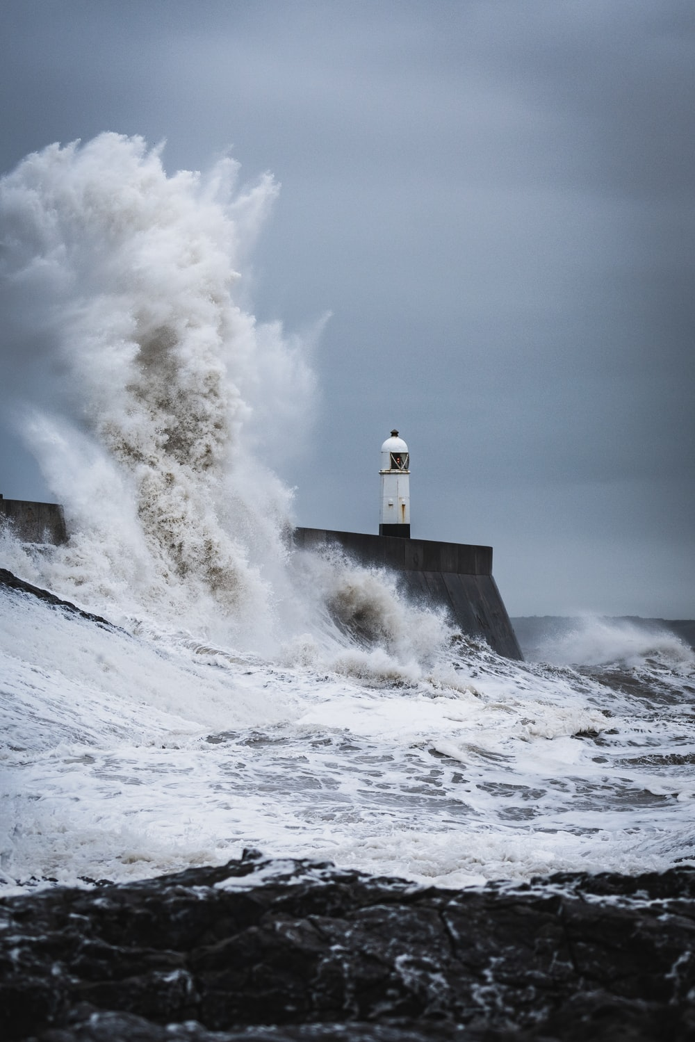 big waves crashing on lighthouse during daytime