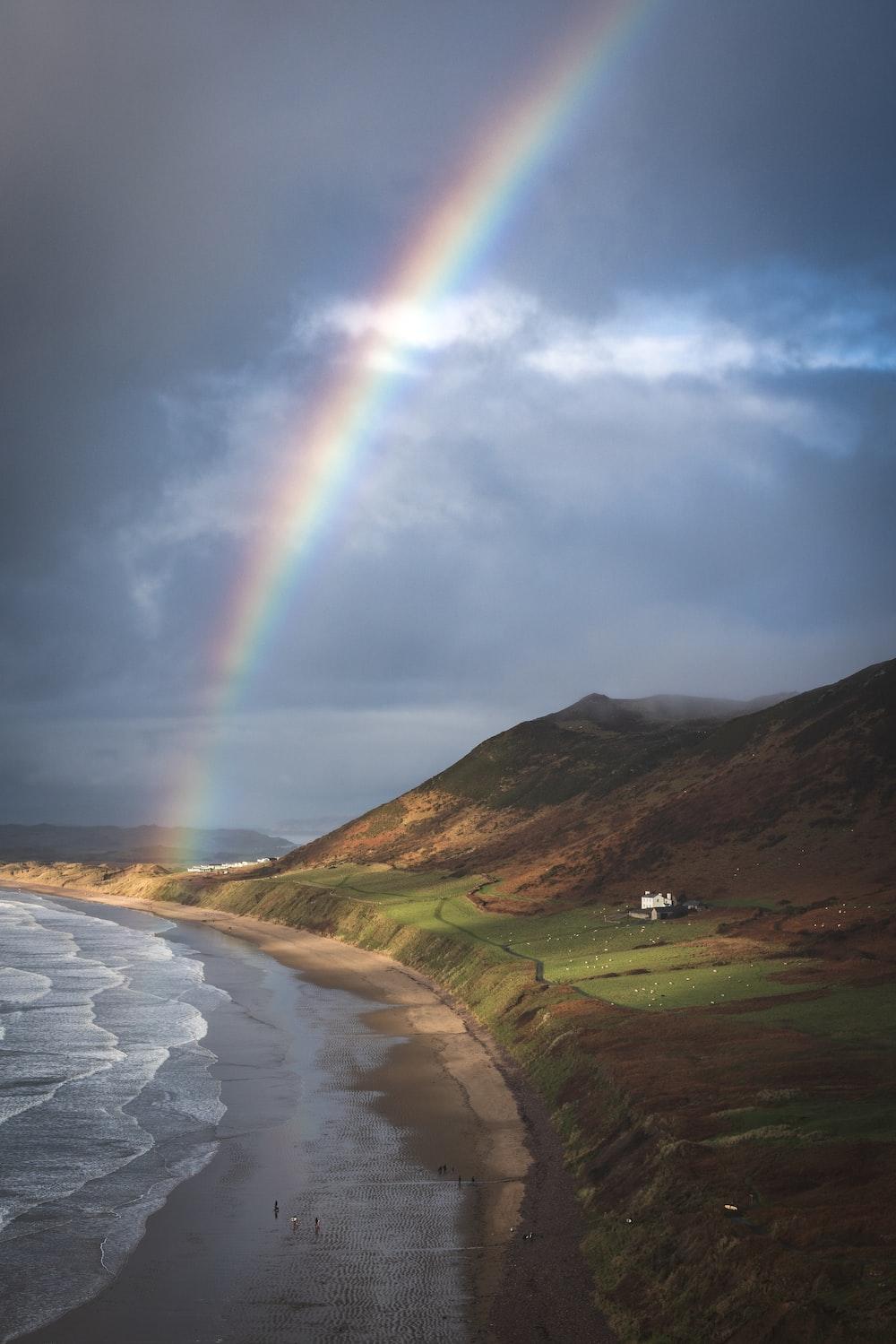 rainbow under cloudy sky
