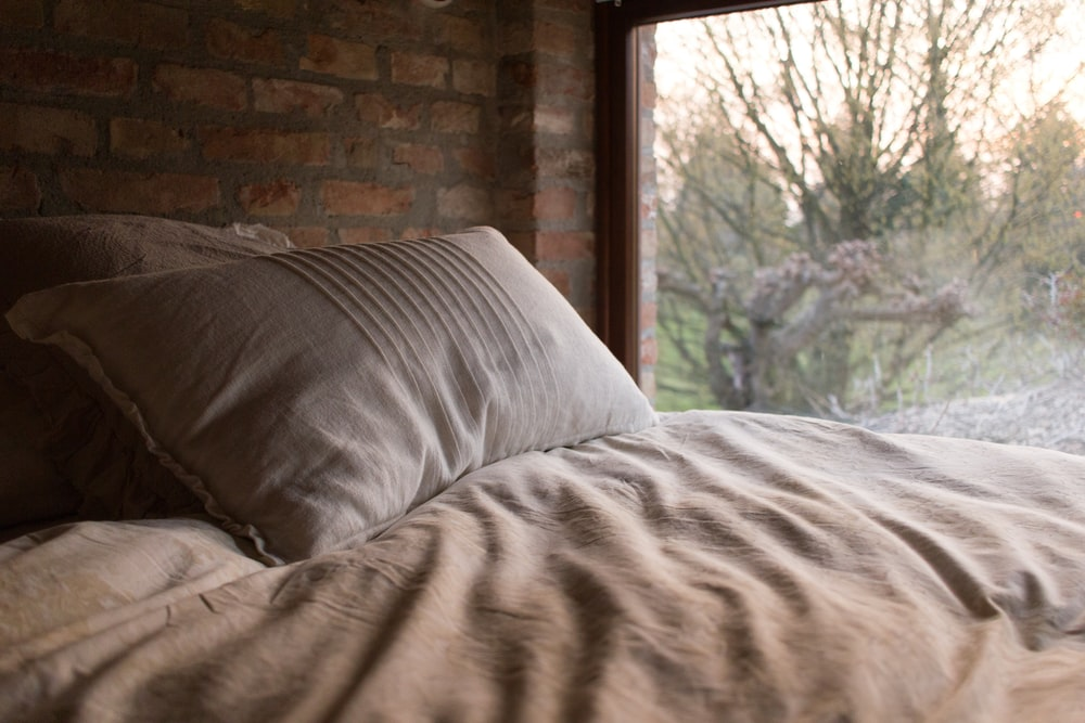 pillow on bed near window