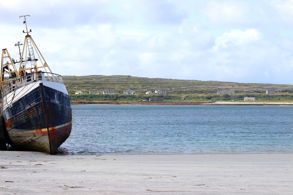 wrecked blue and white boat on shore at daytime