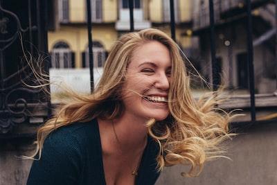 woman smiling near wall