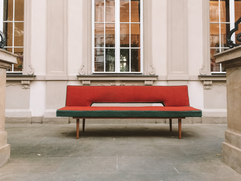 vacant red and green fabric armless futon outside white concrete building