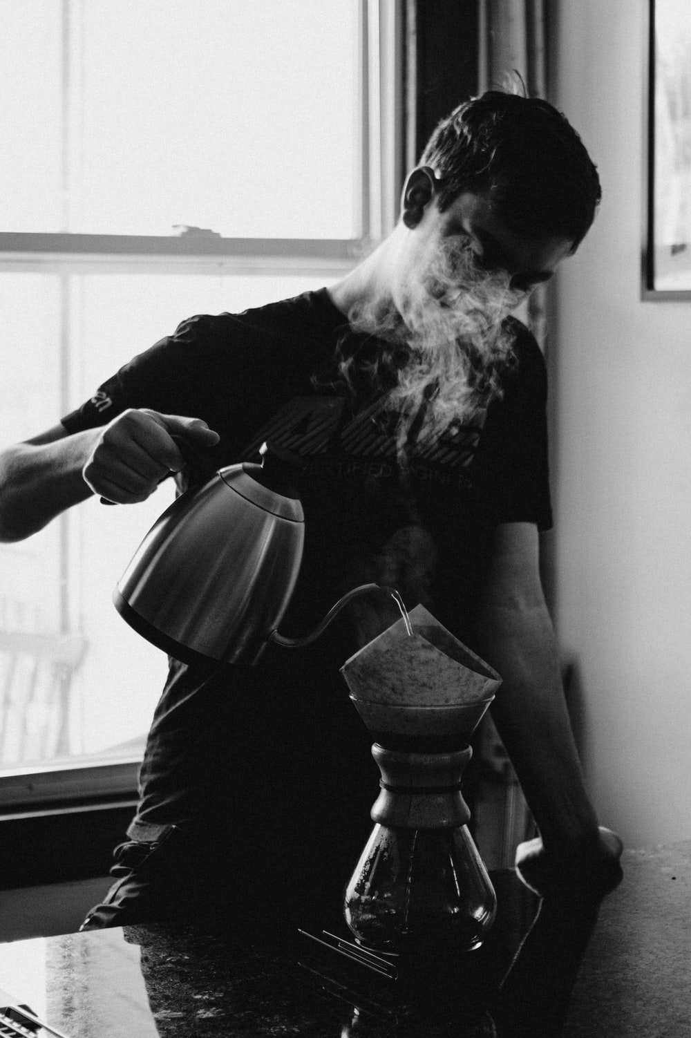 grayscale photography of man holding kettle