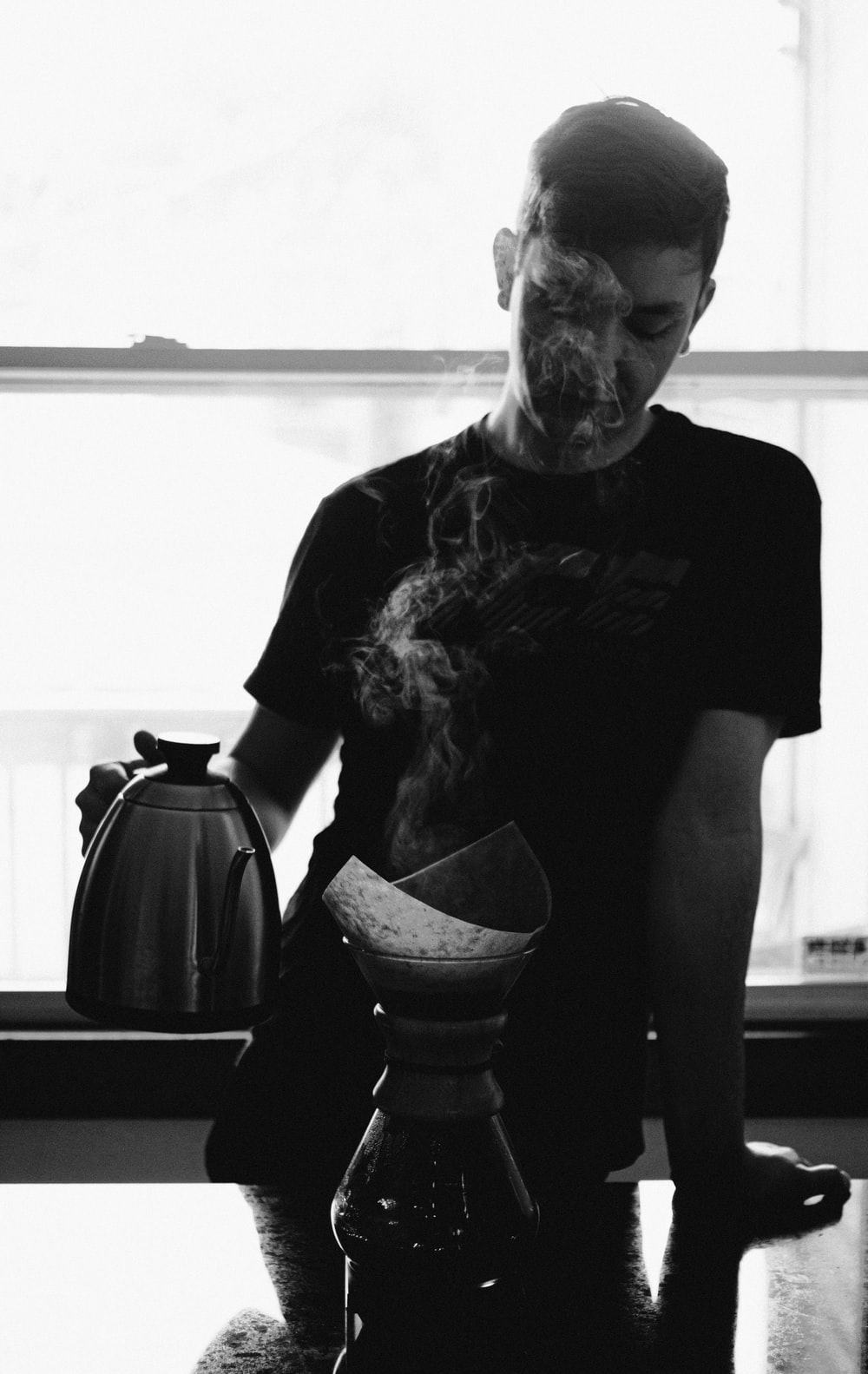 greyscale photography of man holding kettle