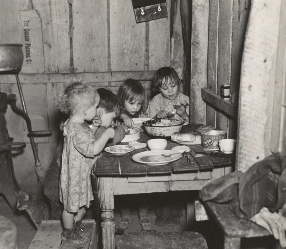 grayscale photography toddlers eating indoors
