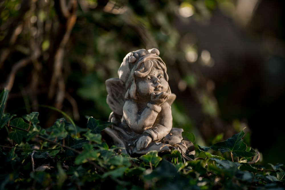 girl leaning forward figurine on green leaves
