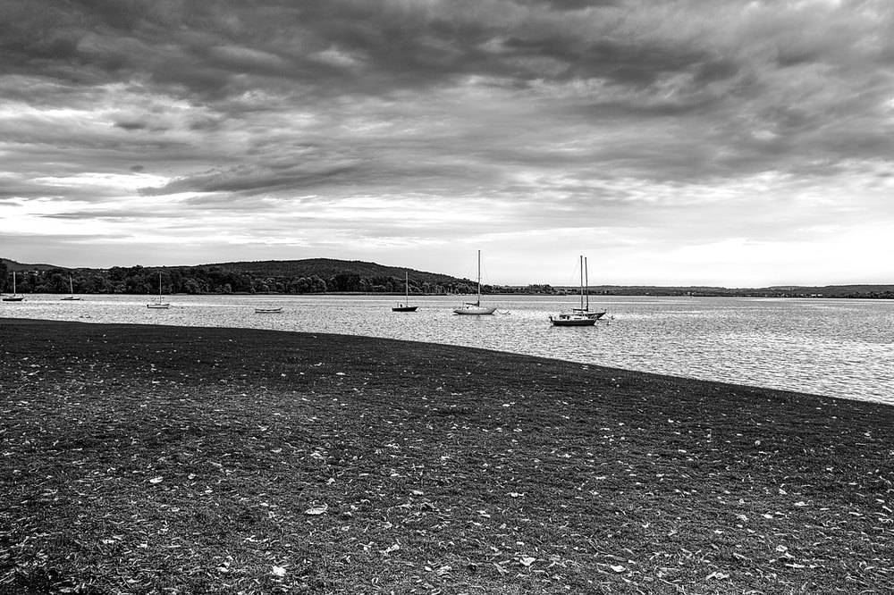 grayscale photography of boats on body of water viewing mountain