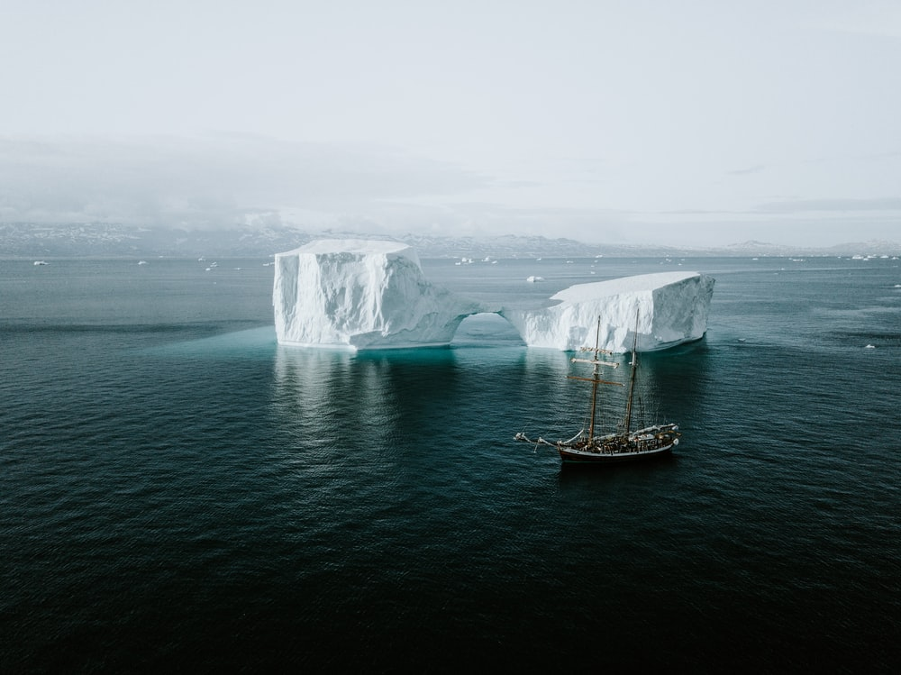 brown and white ship near iceberg
