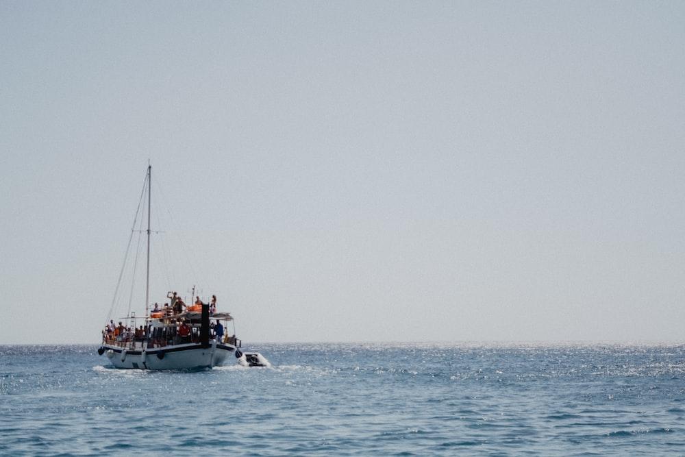 filled boat at sea under gray skies