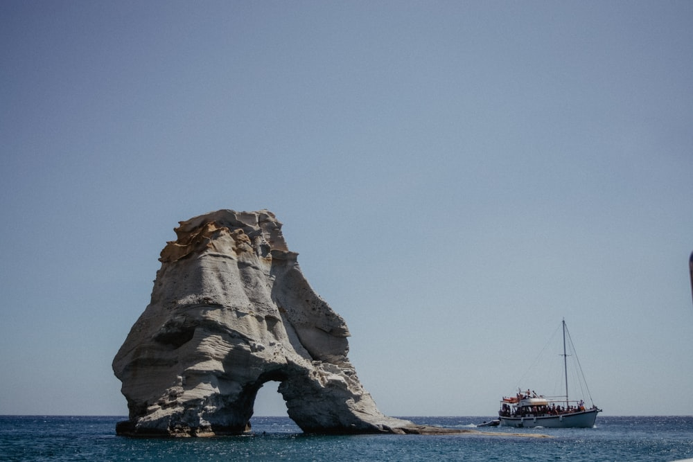 boat by rock formation at sea during daytime