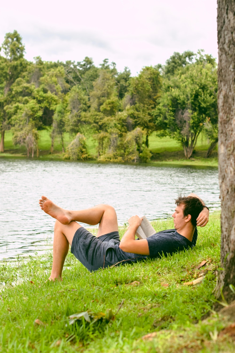 man on grass while reading book
