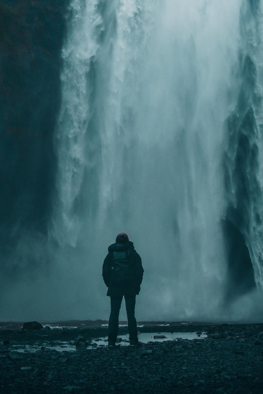 backpacker facing a waterfall