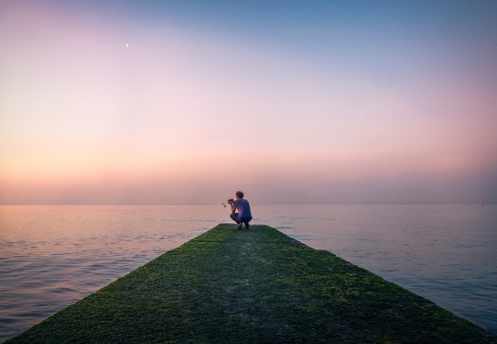 man sitting beside body of water