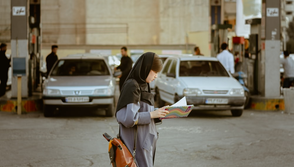 woman reading book while walking on street
