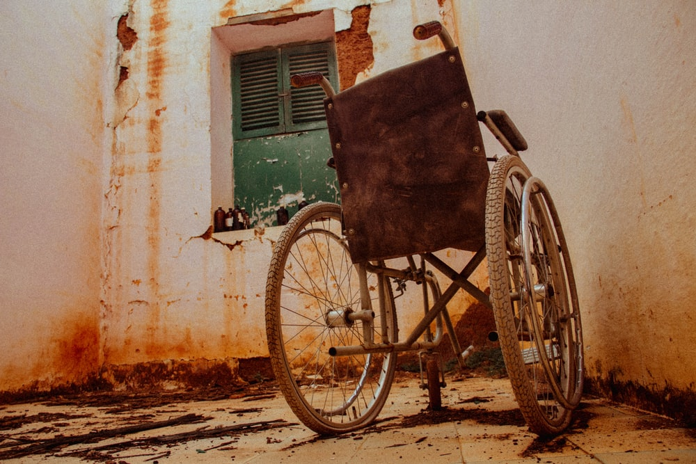 gray wheel chair beside wall