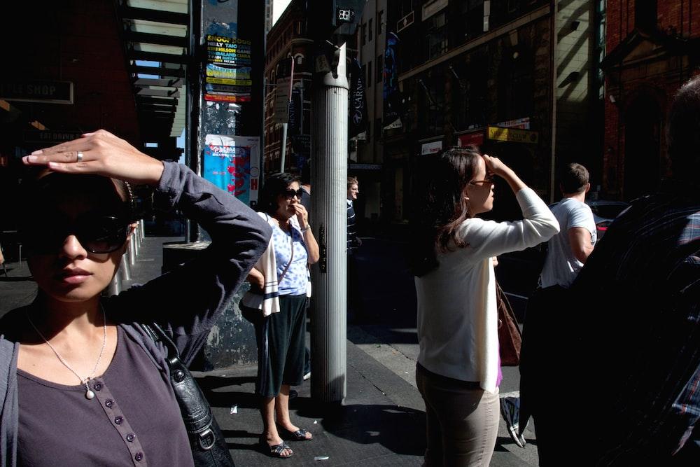 woman wearing white long-sleeved shirt walking on street