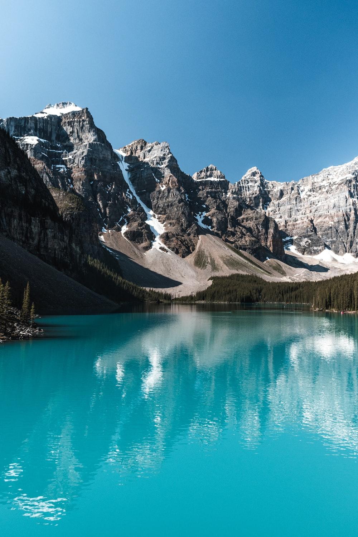 grey mountain beside body of water
