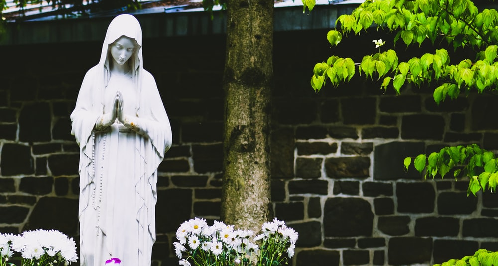 gray Virgin Mary statue surrounded by flowers