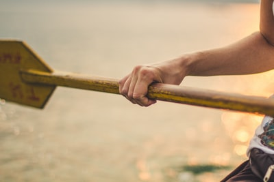 person holding wooden boat paddle