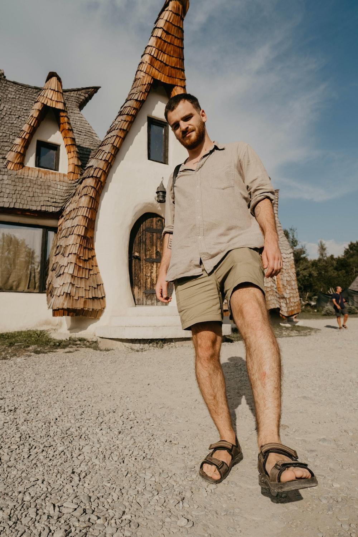 man wearing grey collared shirt standing on pavement