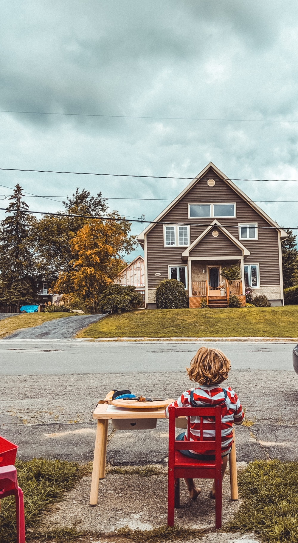 boy sitting on red chair facing near house