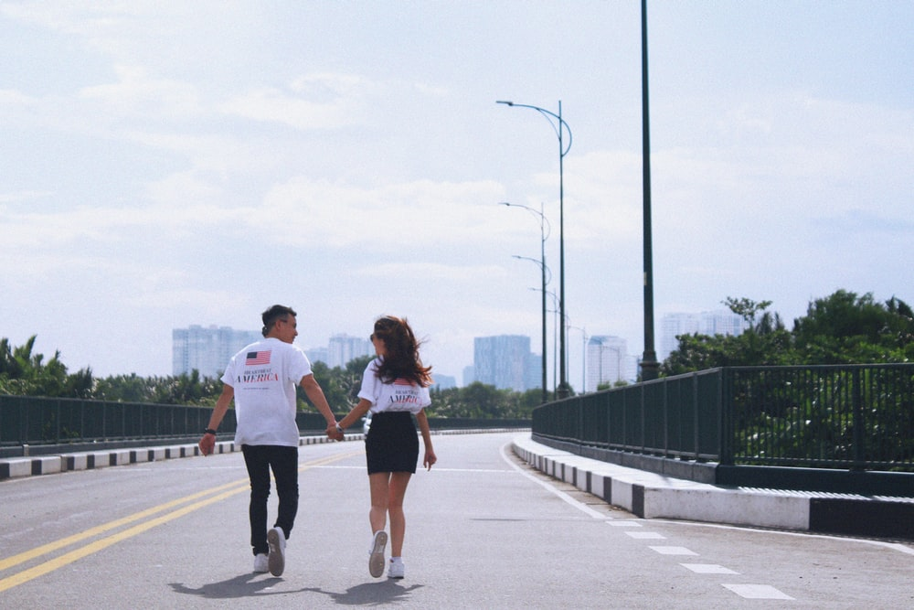 man and woman holding hands while walking on street