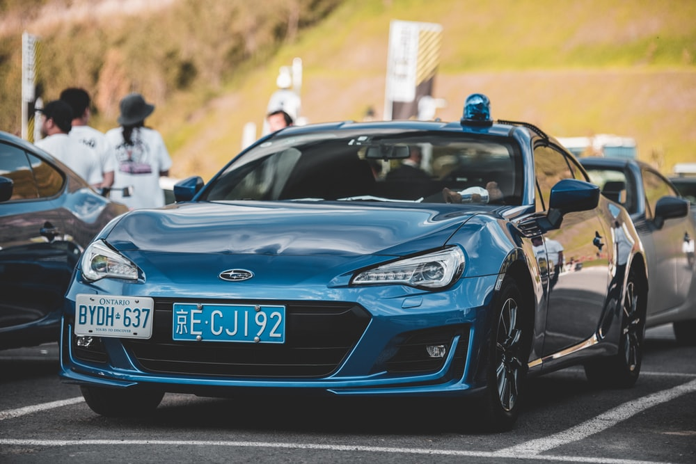 photo of blue coupe on parked