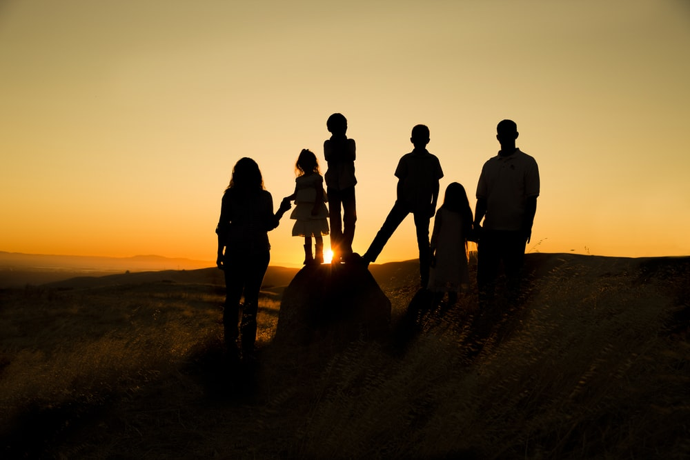 silhouette photography of family during golden hour