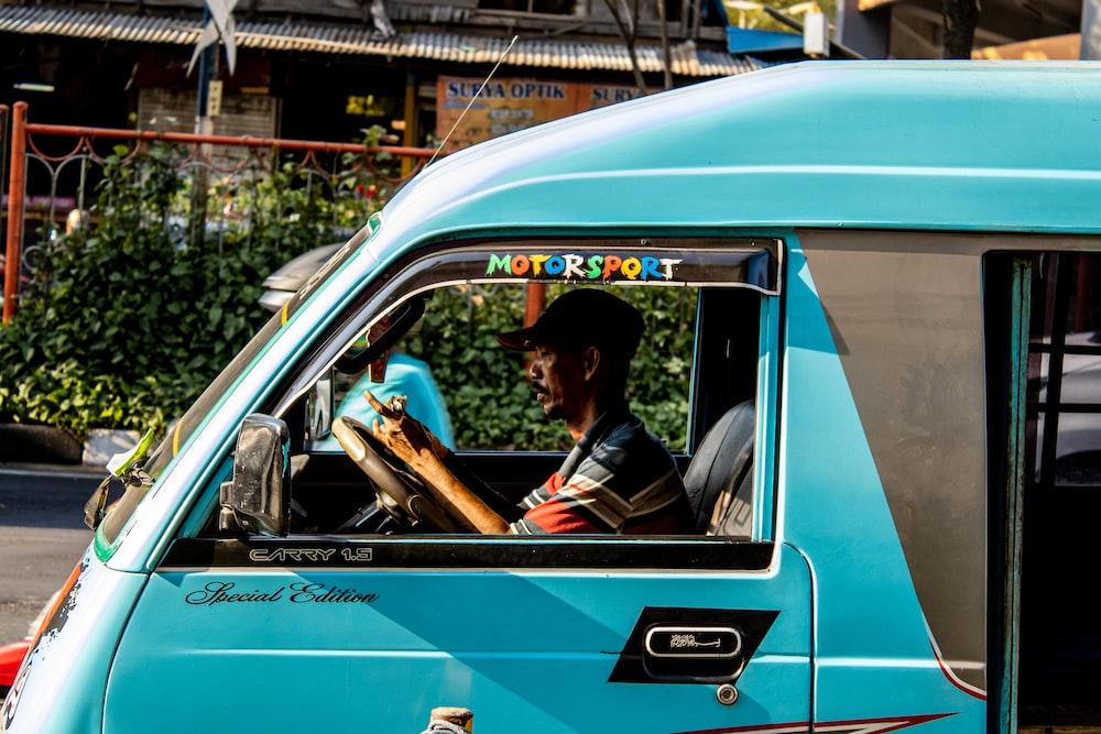 man riding teal enclose van