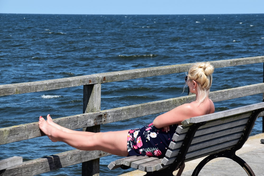 woman sitting on bench facing on body of water