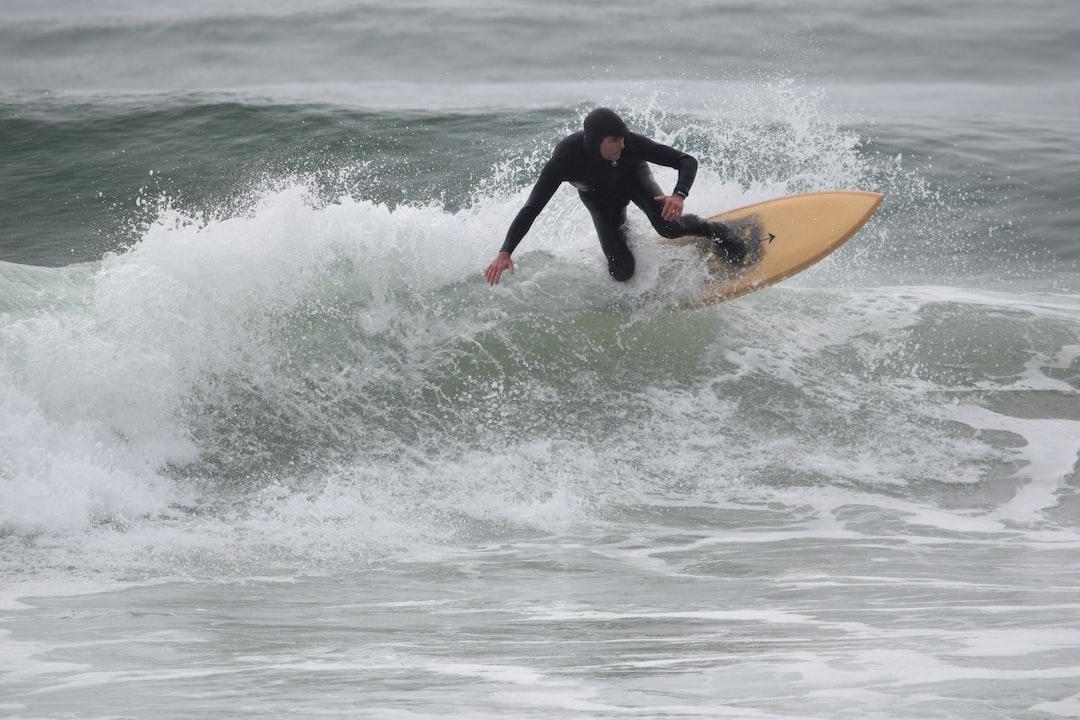 A man surfing on a light brown surfboard.