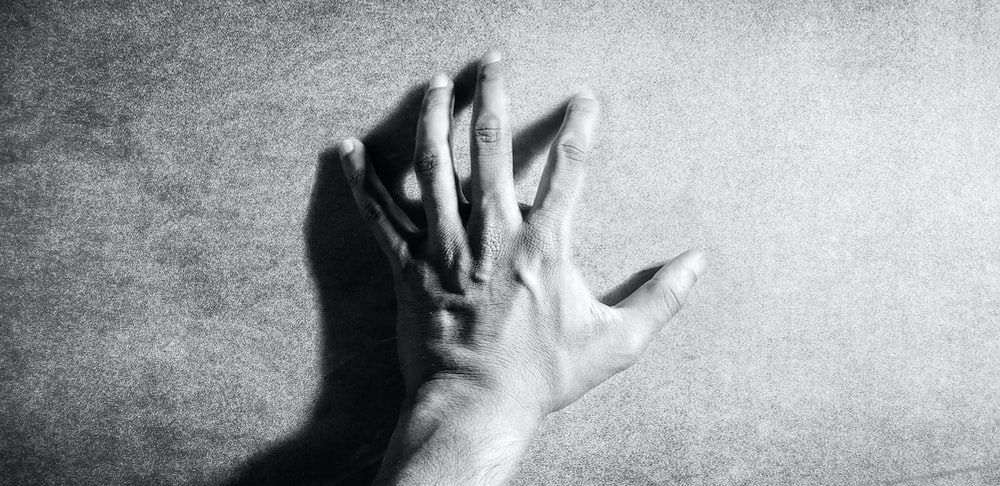left human hand in grayscale photography