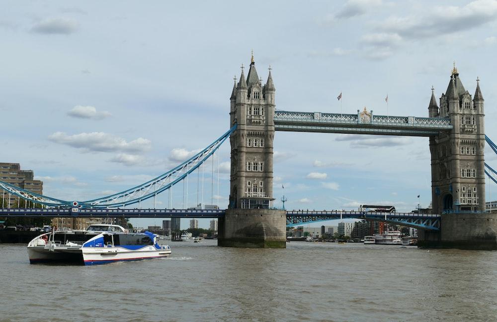 white motorboat near to bridge