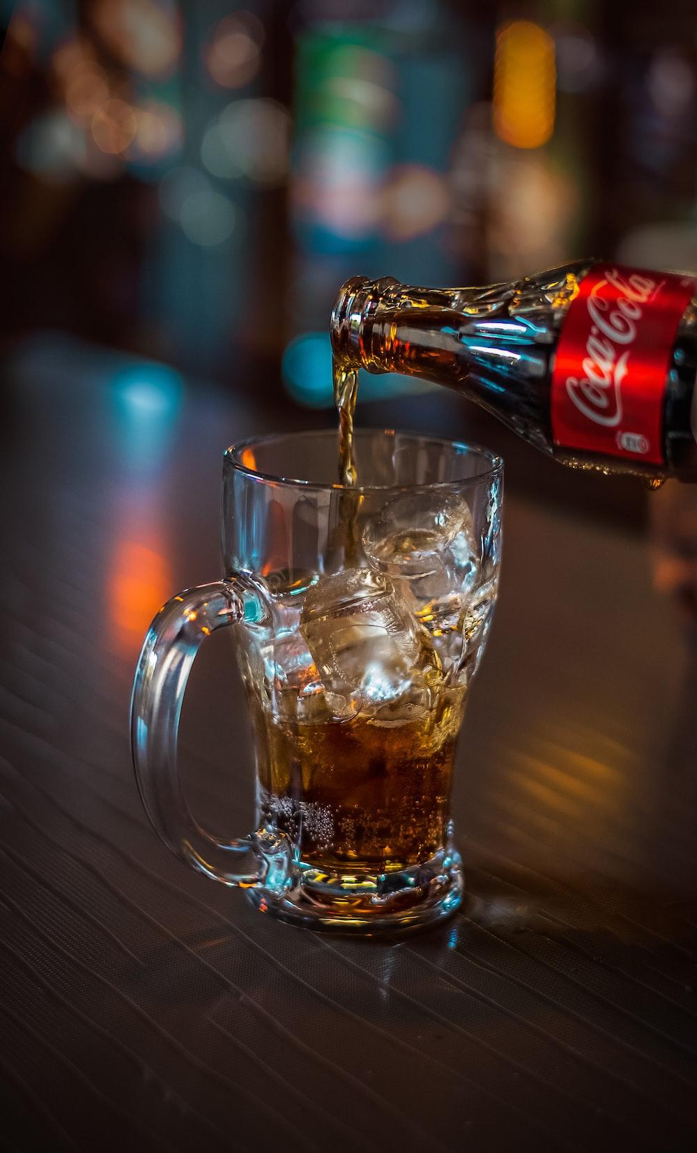 Coca-Cola soda pouring onto clear glass mug