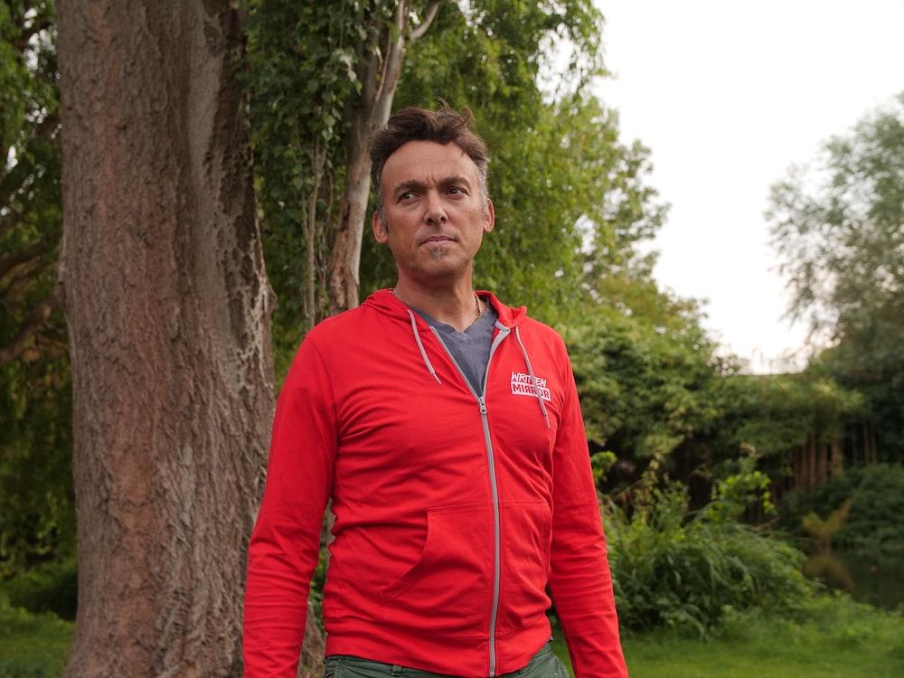 man wearing red zip-up jacket