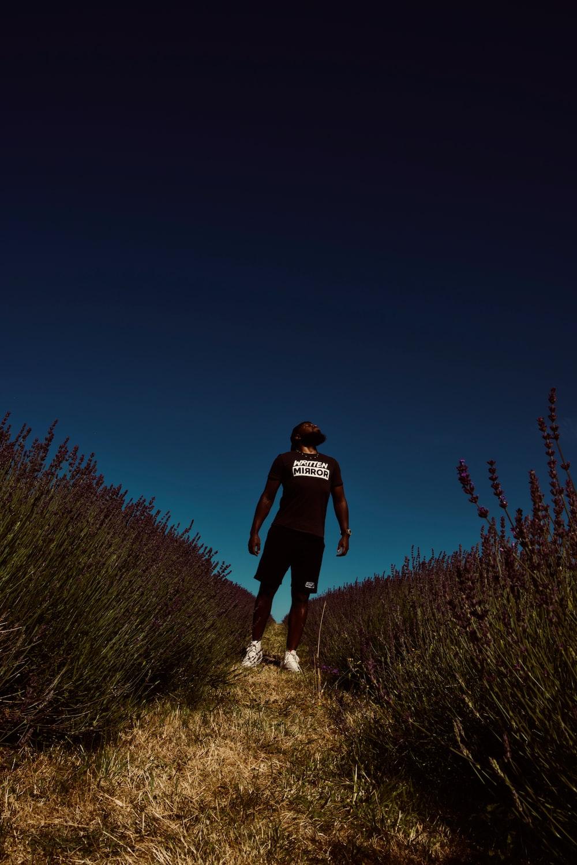 man standing between of grass field at daytime