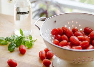 red tomatoes in round white strainer near green mint and glass bottle on table