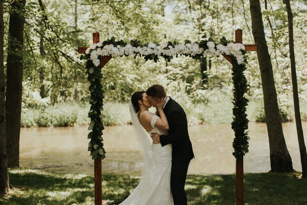 newly wed couple kissing on lips near lake surrounded with tall and green trees